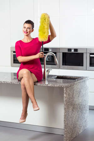 Happy elegant woman holding a dust brush sitting on a kitchen worktop Stock Photo