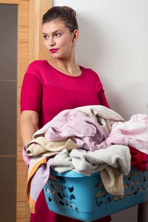 pedantic: Elegant housewife holding heavy laundry basket Stock Photo