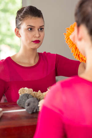 mujeres tristes: Sad woman cleaning a big mirror using a microfiber glove