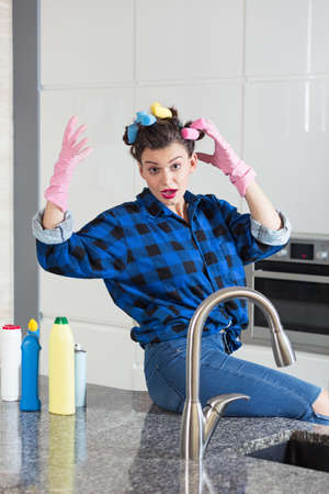 pedantic: Woman with a hair rollers wearing a cleaning gloves sitting on a kitchen worktop