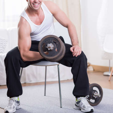 Smiled and satisfied man training on a gym with irons