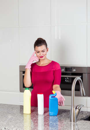 pedantic: Beautiful woman wearing cleaning gloves standing in a light kitchen interior
