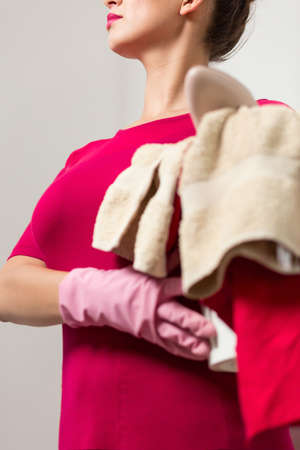 pedantic: Shot of an elegant woman with laundry wearing cleaning gloves Stock Photo