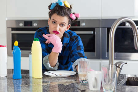 hair rollers: Bored woman with a hair rollers standing in a light kitchen interior