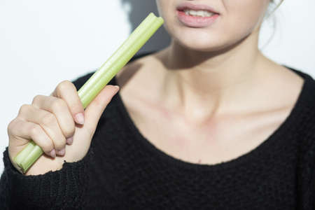 maturation: Close up of an anorexic girl eating a leek Stock Photo