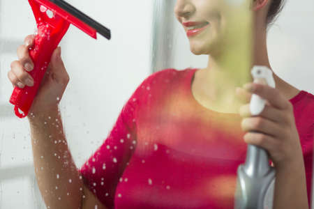 pedantic: Close up of a happy woman cleaning a window