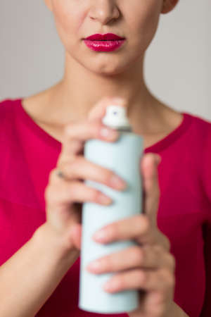pedantic: Close up of an elegant woman holding a bug spray