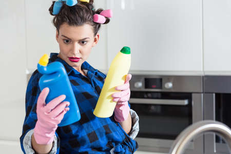 pedantic: Woman with a hair rollers holding two bottles of cleaners