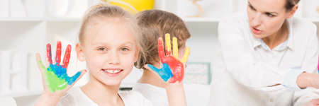 painted hands: Portrait of girl with colorful painted hands