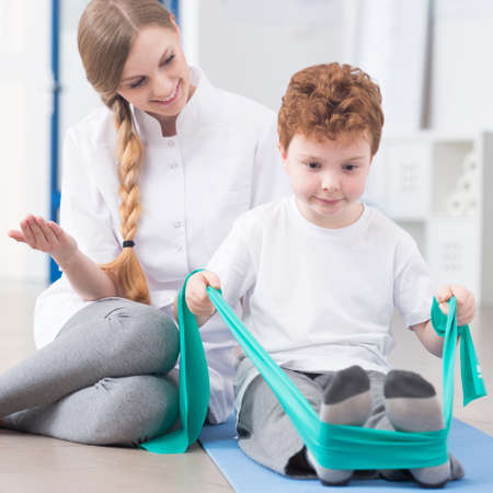 Young physiotherapist and child participating in rehabilitation Stock Photo