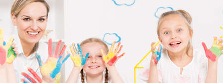 painted hands: Teacher and girls showing color painted hands Stock Photo