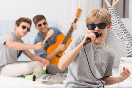 Happy boy wearing sunglasses singing to microphone Stock Photo