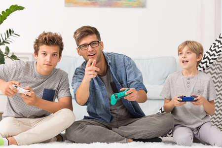 jugando videojuegos: Padre y sus hijos la celebración de los controladores, jugando juegos de video