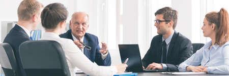 Biuro zespół siedzi razem przy biurku i patrząc na innego mówiącego szefa, siedzi w środku