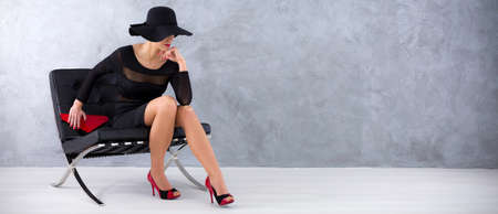 clutch cover: Woman in black dress, with black hat eclipsing her eyes and red clutch in her hand, sitting on a modern armchair against grey wall Stock Photo