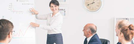 brain storming: Young woman making a presentation to other office employees, showing some details on a board with charts Stock Photo