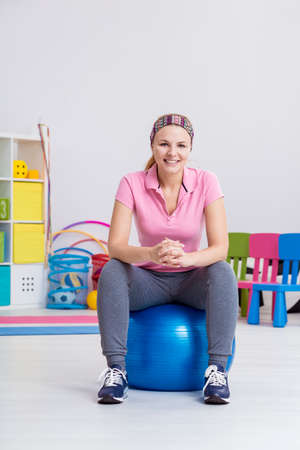 gym ball: Happy woman sitting on a gym ball in light interior