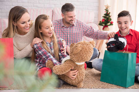 family couch: Happy children with gristmas gifts and their parents sitting together