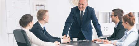事務所チーム一緒に机に座って、それらの近くに立っている他の話す従業員を見て