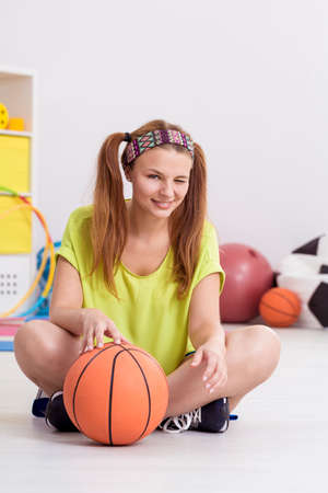 Slim teenager winking, sitting on floor with basketball Stock Photo
