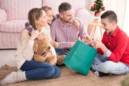 Happy family sitting on carpet, boy opening christmas gift bag