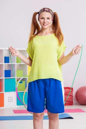 saltar la cuerda: adolescente deportivo llevando la venda que ejercita con la cuerda de saltar