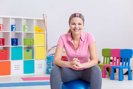 gym ball: Smiling woman physiotherapist sitting on gym ball Stock Photo