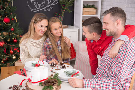 beside table: Family sitting beside table in decorated room celebrating christmas eve Stock Photo