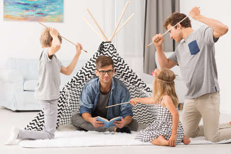 living room sofa: Father sitting in tent playing with children at home