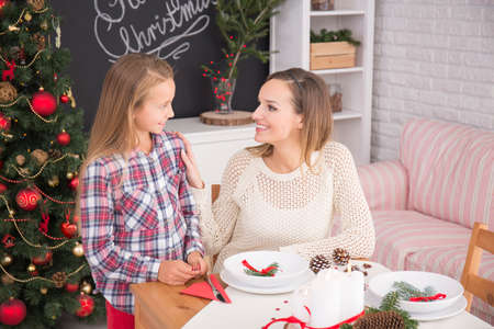 beside table: Mother and daughter beside table decorated for christmas eve