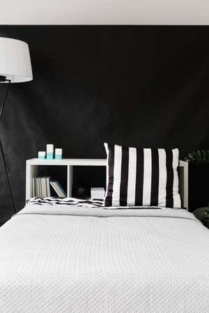 ingenious: Large comfortable white bed standing on the background of the black sheet