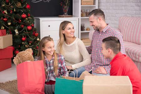 christmas gift box: Family sitting on floor beside christmas tree among christmas presents Stock Photo