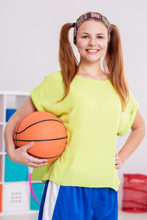 ponytails: Active teenager with two ponytails and headband holding basketball