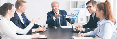 equipo de oficina sentados juntos en un escritorio y mirando a otro, empleado anciano les muestra el gráfico de Foto de archivo