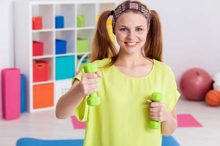 ponytails: Happy teenager with two ponytails exercising with dumbbells