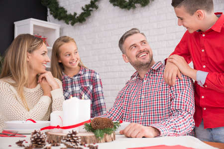 beside table: Happy family beside table in christmas dining room