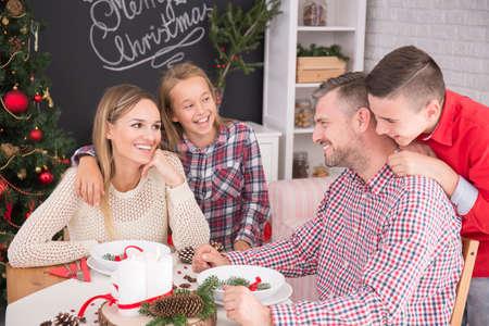 beside table: Happy family sitting beside table during christmas dinner