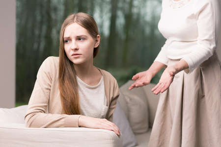 Sad teenage girl sitting on a sofa and her mother standing above her