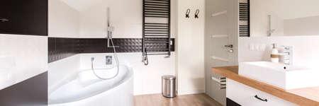handbasin: Minimalist and modern bathroom in black and white, with corner bath, black heater and rectangular handbasin