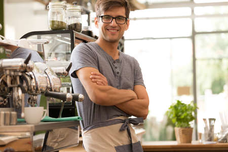 machine man: Shot of a happy young barista standing next to a coffee machine