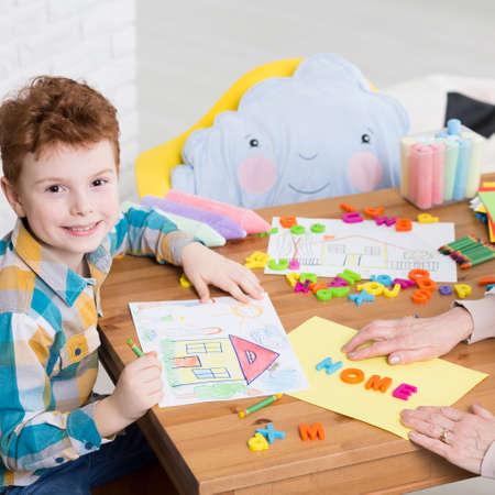 Dibujando una casa durante la terapia ocupacional Boy Foto de archivo - 68991821