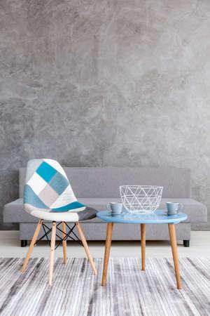 Acetische stijl woonkamer met grijs cement muur effect, bank, lapwerk stoel, twee kopjes staan op een kleine tafel