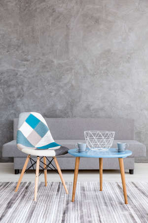 Acsetic style living room with grey cement wall effect, sofa, patchwork chair, two cups standing on a small table