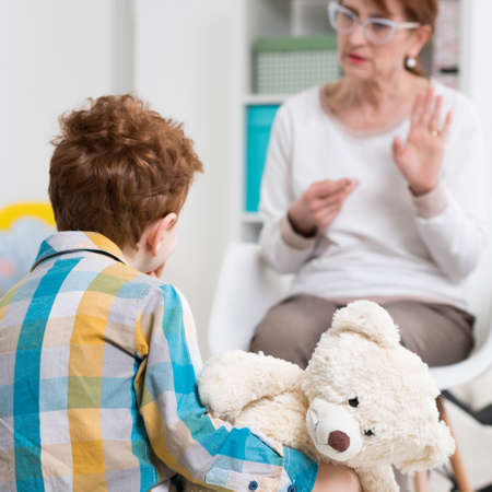 Pedagogue talking with a child in the office