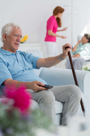 Resident of nursing home holding walking stick and remote control
