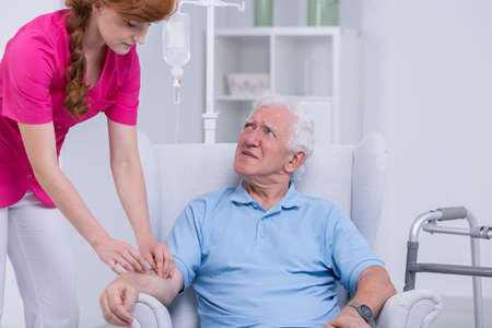 man sit: Carer checking intravenous drip of senior patient Stock Photo