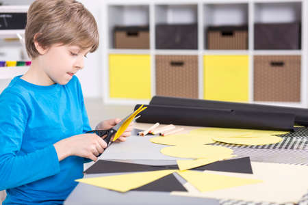 Focused and creative boy is cutting piece of paper