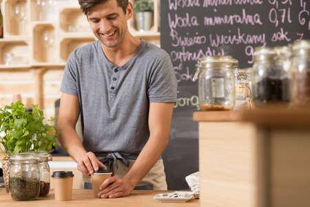 Yyoung barista preparing coffee to go in a cozy coffee house
