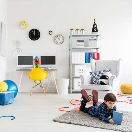 boy bedroom: Shot of a little boy reading a book in his bedroom Stock Photo