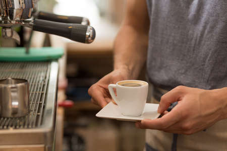 place of work: Cropped picture of a barista serving a small cup of esspresso